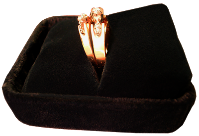 An engagement ring and wedding band in black velvet box.