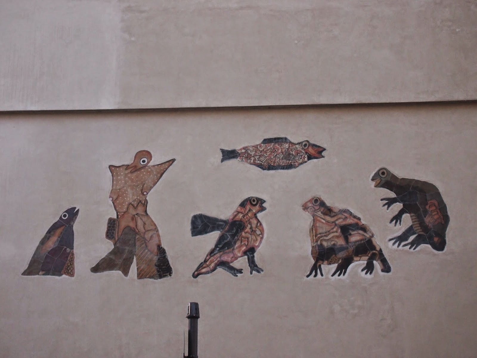 strange looking animals painted in earth tones on a building in copenhagen