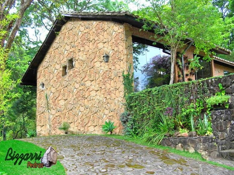 Calçamento com pedras rústicas na entrada do carro na construção da residência com os muros de pedra, a parede de pedra e a execução do paisagismo.