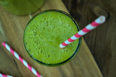 A Beginners Guide to Juicing - Green mango smoothie from above with stripey paper straw on wooden board
