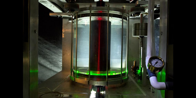 Water-filled version of MRI experiment showing transparent outer cylinder and blackened inner cylinder. Red lasers enter at bottom to measure the local speed of the water. (Photo courtesy of Eric Edlund and Elle Starkman)