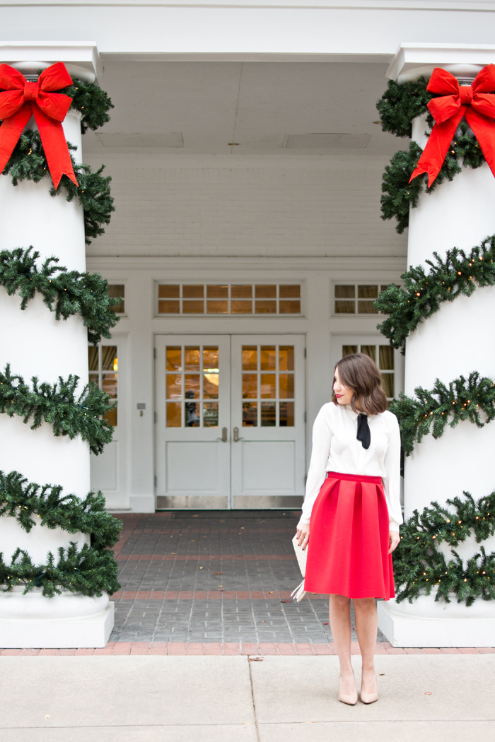 christmas eve outfit idea, holiday party look, outfit ideas, red midi skirt, midi skirt, pussybow blouse, nude heels, midi skirt