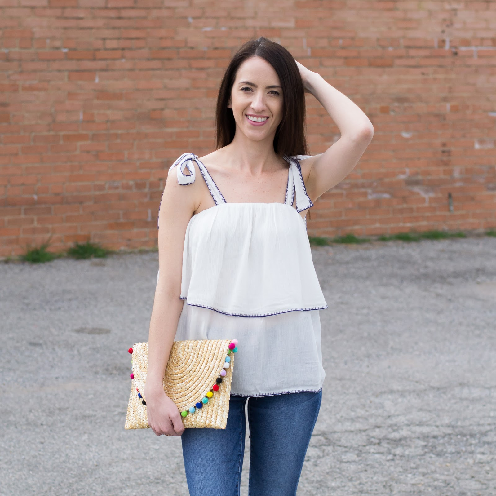 White ruffle top and straw pom clutch