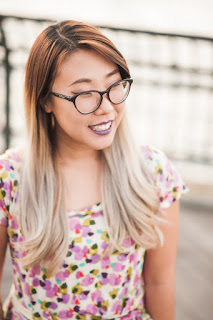 Image of Franny Choi smiling to the right of the camera. She wears an abstract, floral print dress in shades of pink, yellow, turquoise and black. She wears a lilac shade of lipstick and softly cat-eyed framed glasses. She has long hair that is dark gold hear her scalp and a very light blonde at the ends.