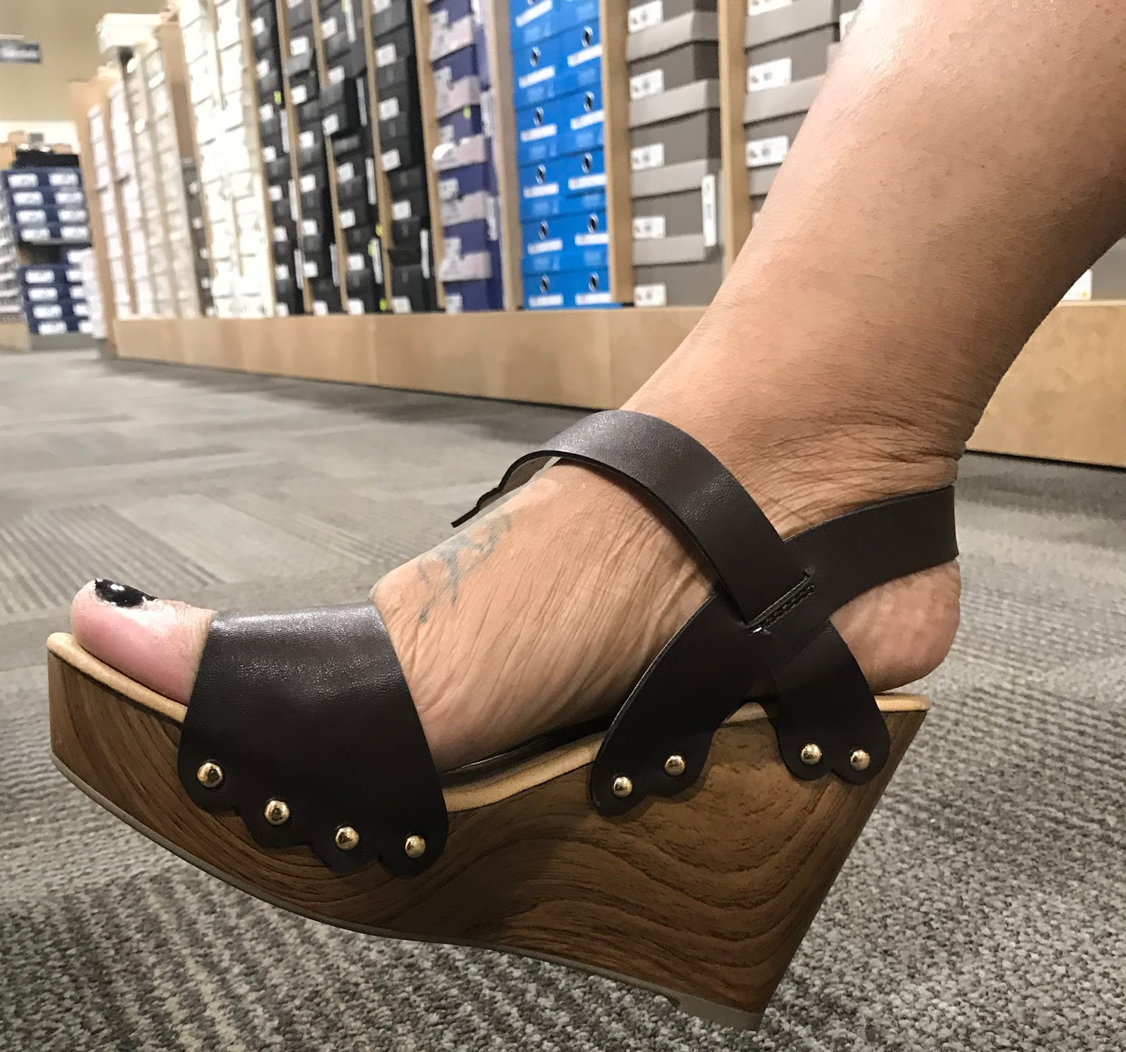 Image: Woman trying on wood shoes for haul. Later I tried on a candy style wood shoe that had a nice high wedge. The bad part was my natural heel was hanging off the back of the shoe.