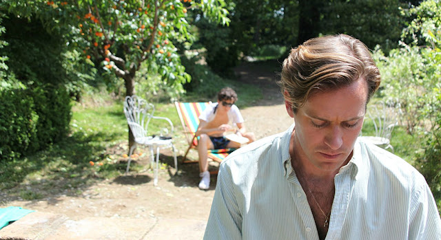 Armie Hammer en primer plano, con Timotheé Chalamet de fondo en una escena de Call me by your name