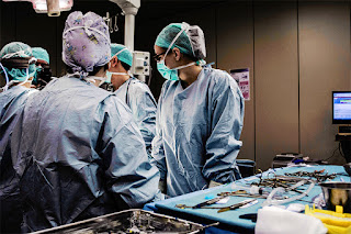 Medical Staff standing in a surgery area wearing blue scrubs