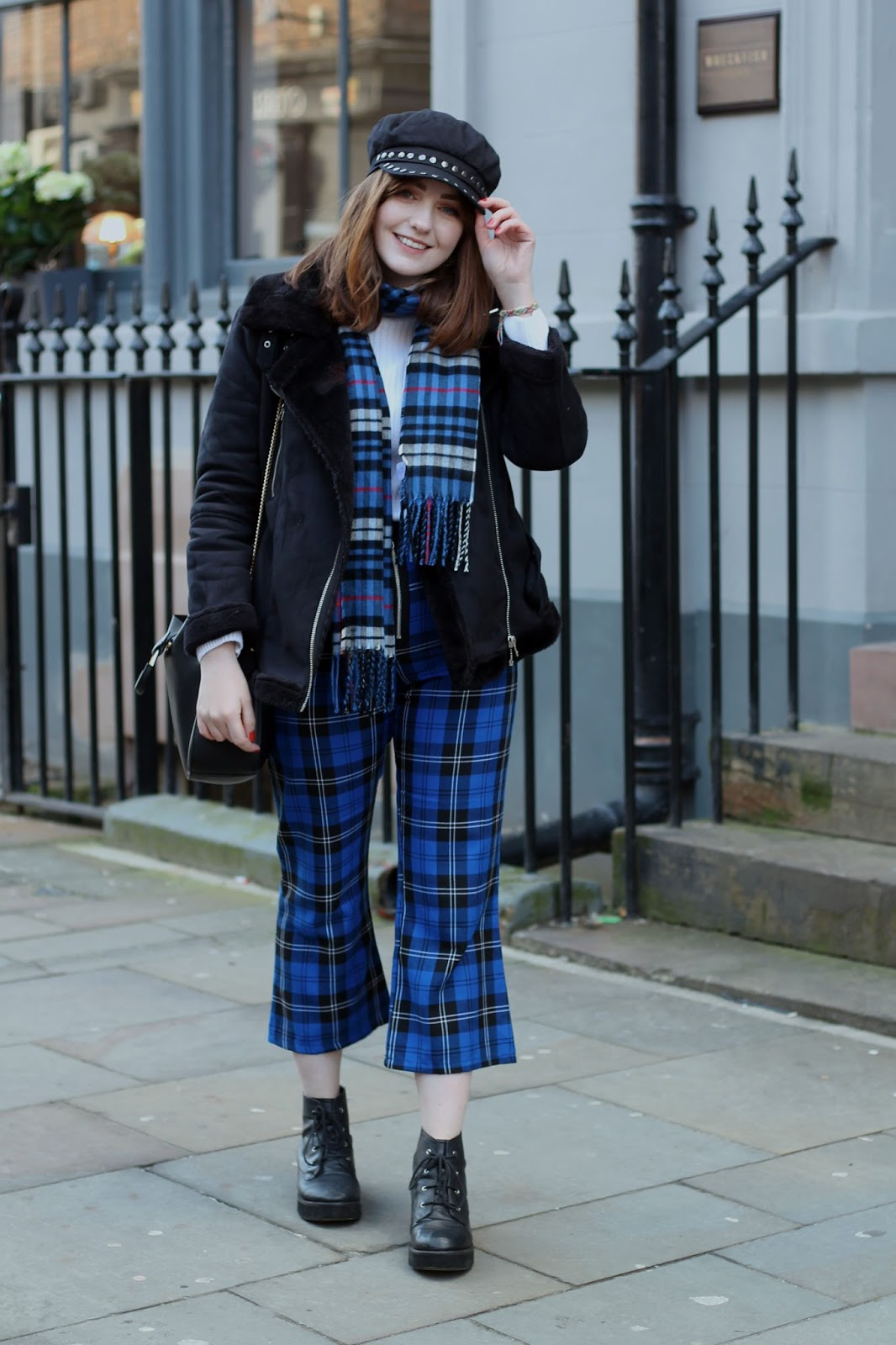 Liverpool style blogger wearing black studded baker boy hat, black aviator jacket, white polo neck jumper, blue tartan scarf, blue tartan kick flare cropped trousers, black lace up boots and black ring detail bag