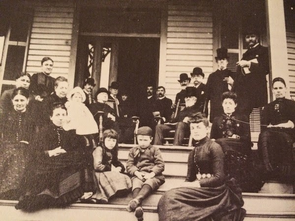 People sitting on porch steps at Leon Hotel, Tallahassee, circa 1886