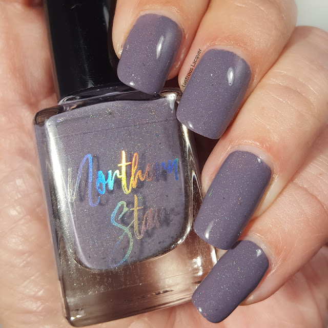 Greyish purple nail polish with scattered holographic glitter