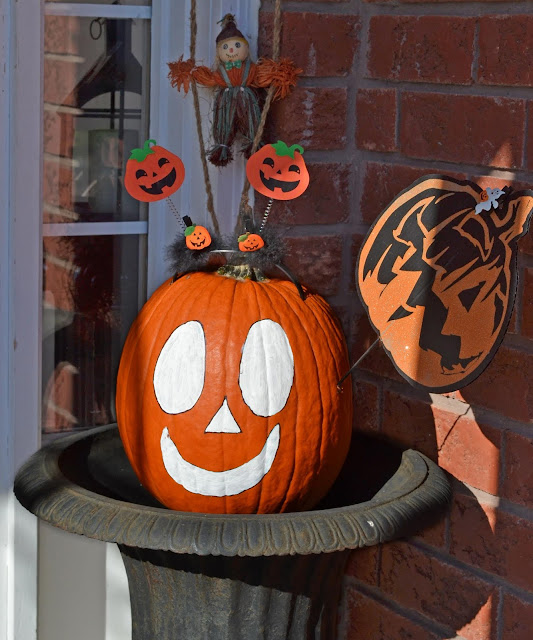 A simple face painted on an uncut pumpkin forms a simple halloween display, with small pumpkins on sticks and a scarecrow riding a rope.