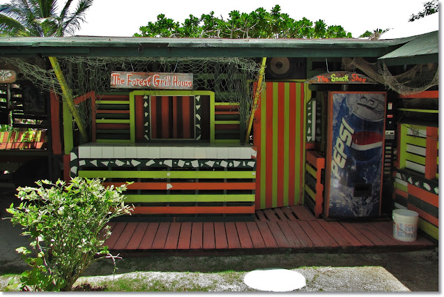 Brightly painted wooden booth, with grill space, Pepsi machine, and service counter.