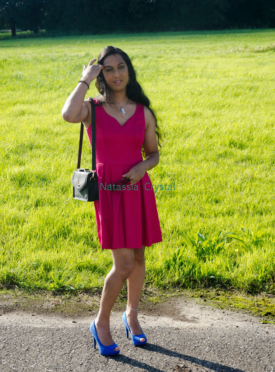 Natassia pink dress blue heels posing grass field