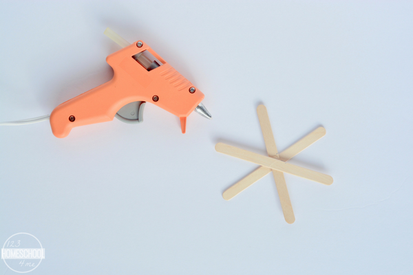 gather Popsicle sticks, a hot glue gun, yellow yarn, and free printable star tags