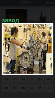 Двое рабочих на заводе на конвейере собирают механизмы