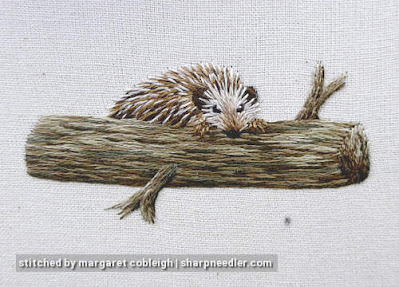 Needlepainted hedgehog climbing over embroidered branch. (Stumpwork and thread painted hedgehog)