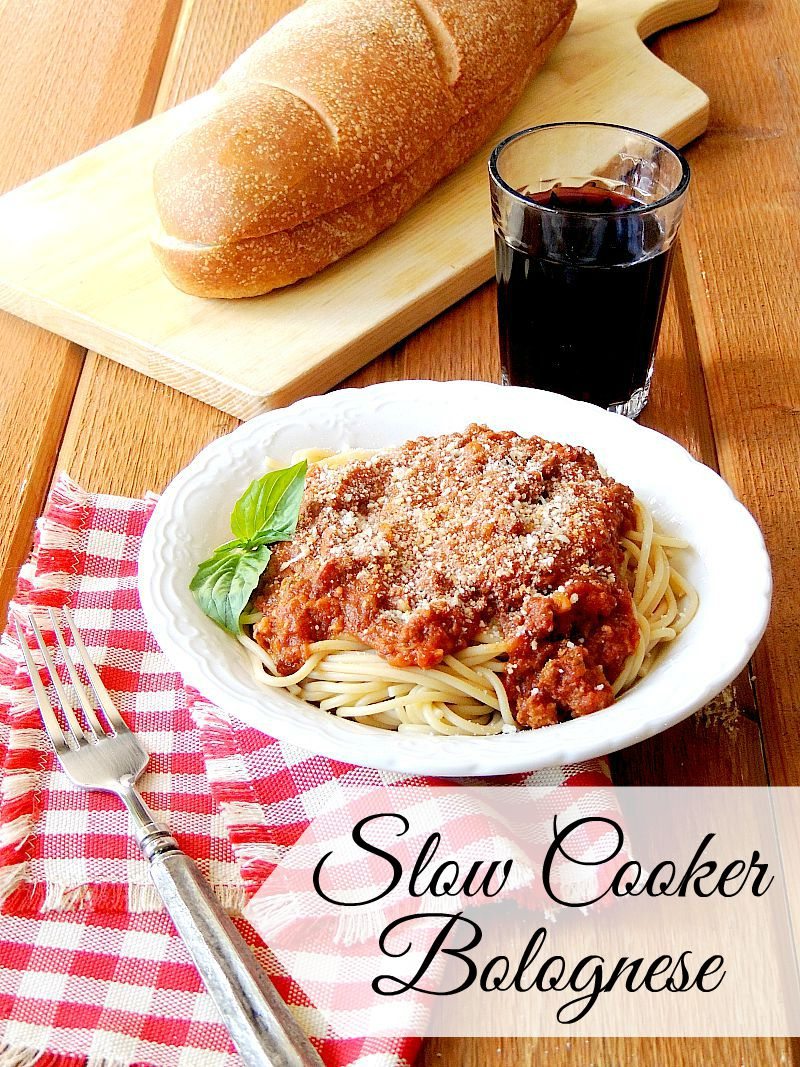 Slow Cooker Bolognese Sauce in a white bowl with a red and white checkered napkin on a wooden table with bread and a glass of wine.