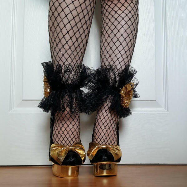gold metallic platform shoes with large bow worn with fishnet tights and handmade lace ankle cuffs