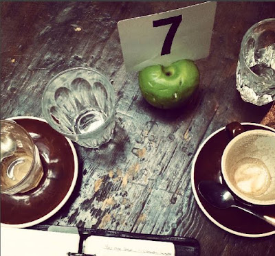 Cafe table from above, with empty coffee cups, glasses and a Filofax planner on it.