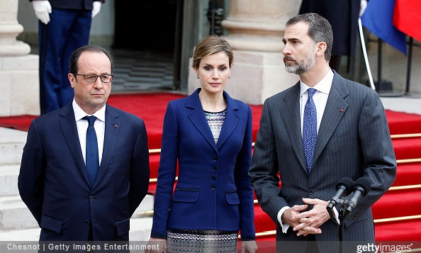 King Felipe of Spain is watched by French president Francois Hollande and Queen Letizia of Spain as he addresses media after a meeting at the Elysee presidential palace