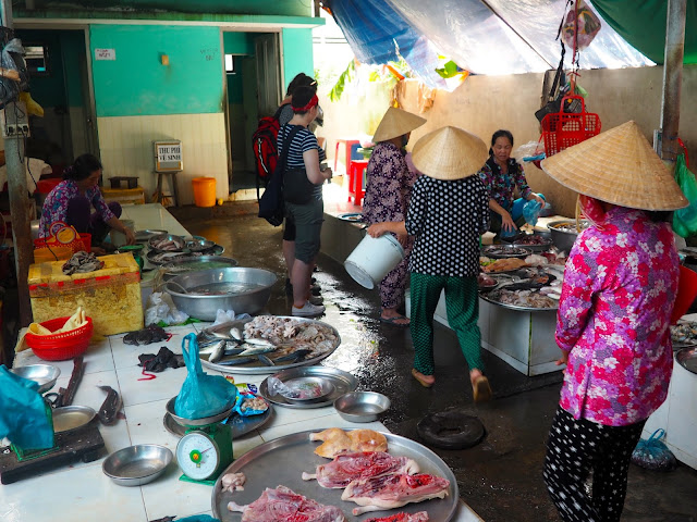 Seafood for sale at the local market, with women wearing traditional Vietnamese hats, in the Mekong Delta, Vietnam