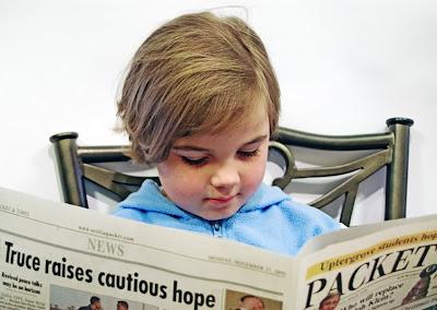Enfant lisant un journal