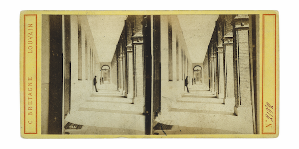 Early twentieth century picture representing one of the corridors adjacent to the central court. Halfway the corridor a man is leaning to the wall. At the back two more figures are visible. The photograph is duplicated and placed on a piece of yellow paper on which the following inscriptions can be found: N°2132, C. Bretagne, Louvain.