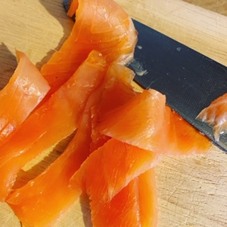 smoked salmon and knife on wooden chopping board