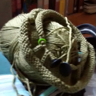 Several rows of knitting in-the-round on circular knitting needles atop 'leaf-green' skein of yarn