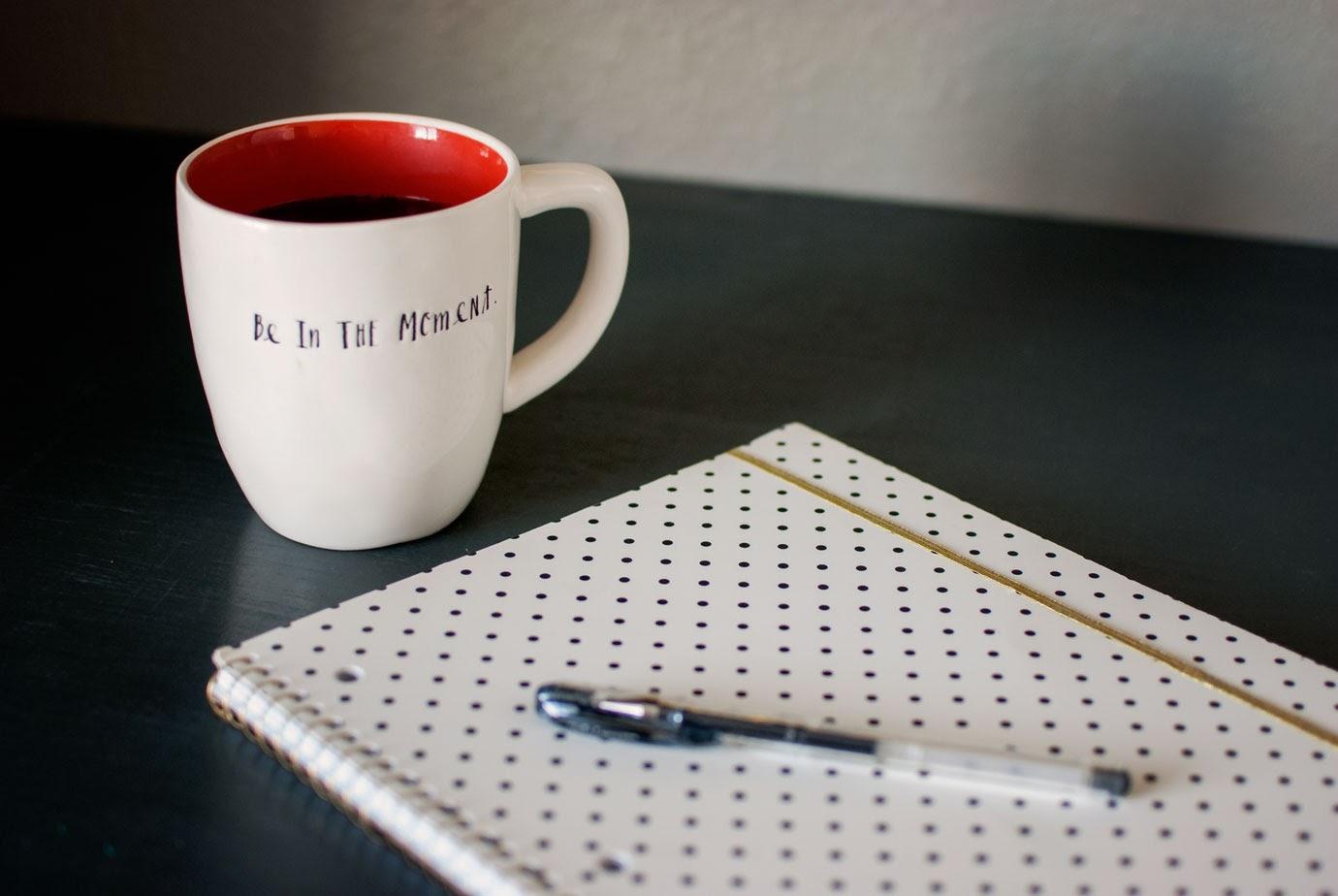 white coffee mug with coffee next to a polka dot notebook with a pen