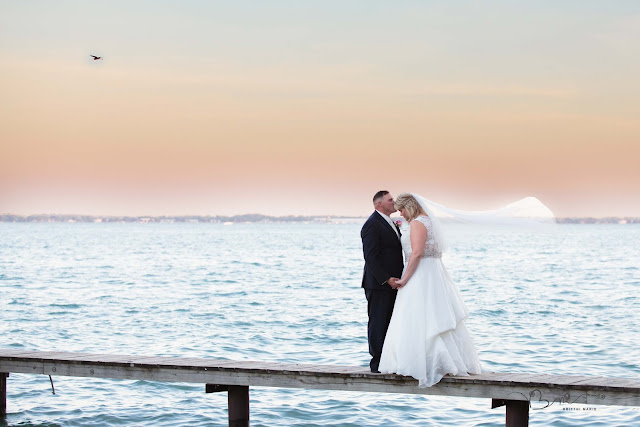 bride and groom on pier at new baltimore waterfront wedding at sunset