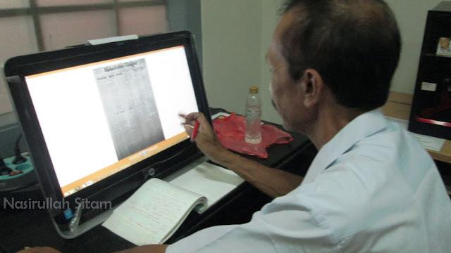 Pak Kindro sedang mengakses koleksi hasil digitalisasi