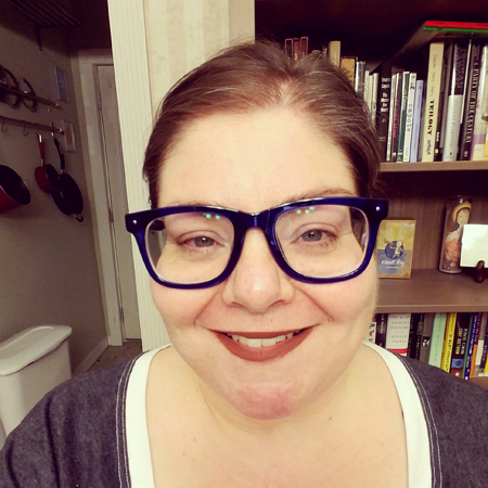 image of me from the shoulders up, sitting at a table in front of a bookshelf, with my hair up and wearing glasses and lipstick