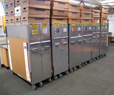 Row of metal-gray cabinets on wheels, piled with cardboard boxes