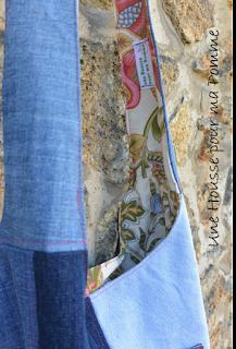 """Sac bandoulière fait de pans de pantalons en jeans recyclés (chinés par mes soins), de différents tons, montés façon patchwork, coutures surpiquées de fil rose, bandoulière en jeans, poche extérieure avec appliqué assorti, entièrement doublé en tissu coton au motif fleuri. Les jeans portés recyclés parfois délavés par le temps apportent cette """"petite chose en plus"""" à cette pièce unique. Dimensions : 35 x 33 x 8 cm, hauteur avec la bandoulière : 83 cm."""