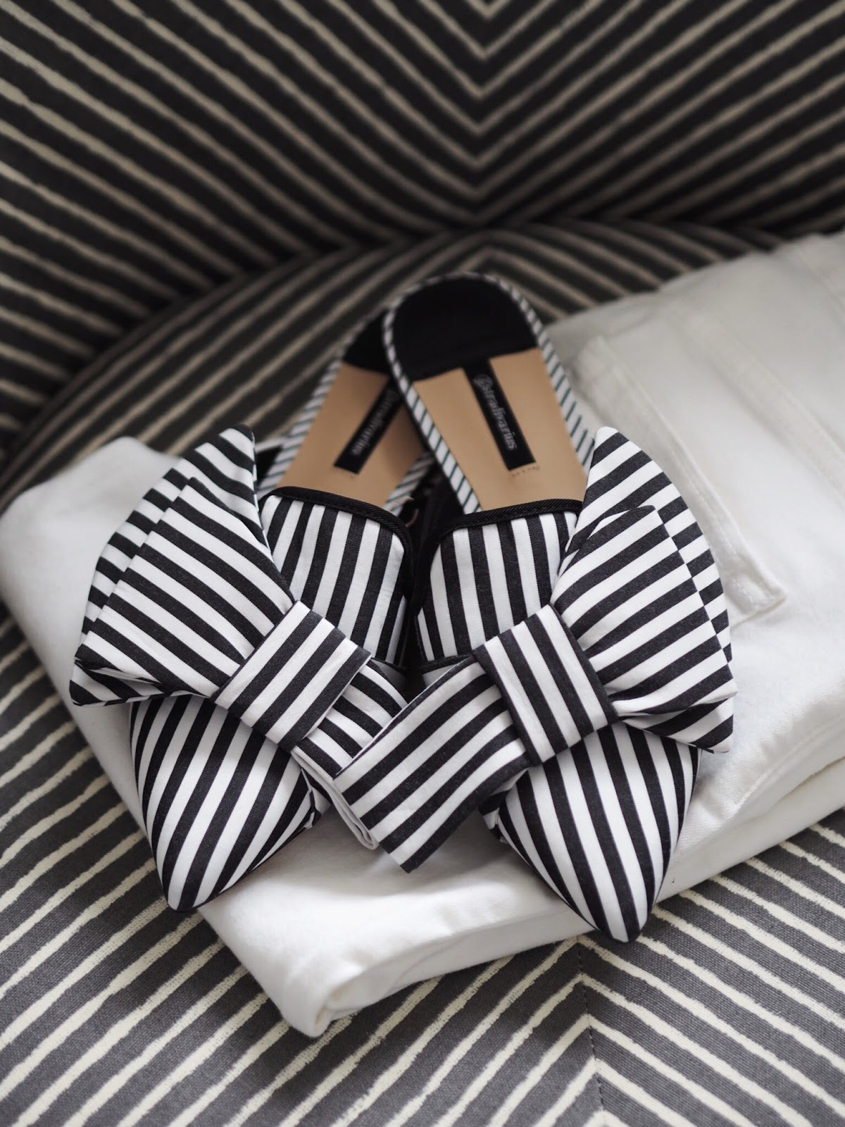 Striped Mules on top of white jeans on striped chair with contrasting stripes
