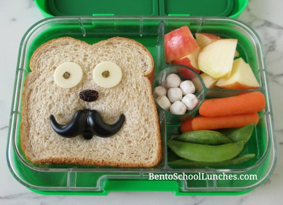 Funny face sandwich lunch with a mustache cupcake ring