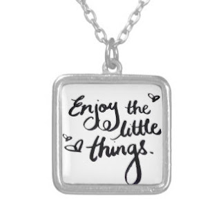 "Handwritten message on pendant saying, ""Enjoy The Little Things."""