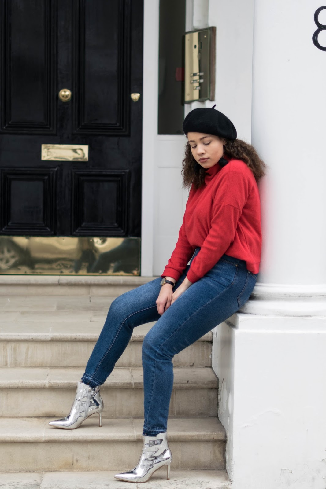 Eboni wearing a red jumper with blue jeans and the silver mirror boots from Pretty Little Thing