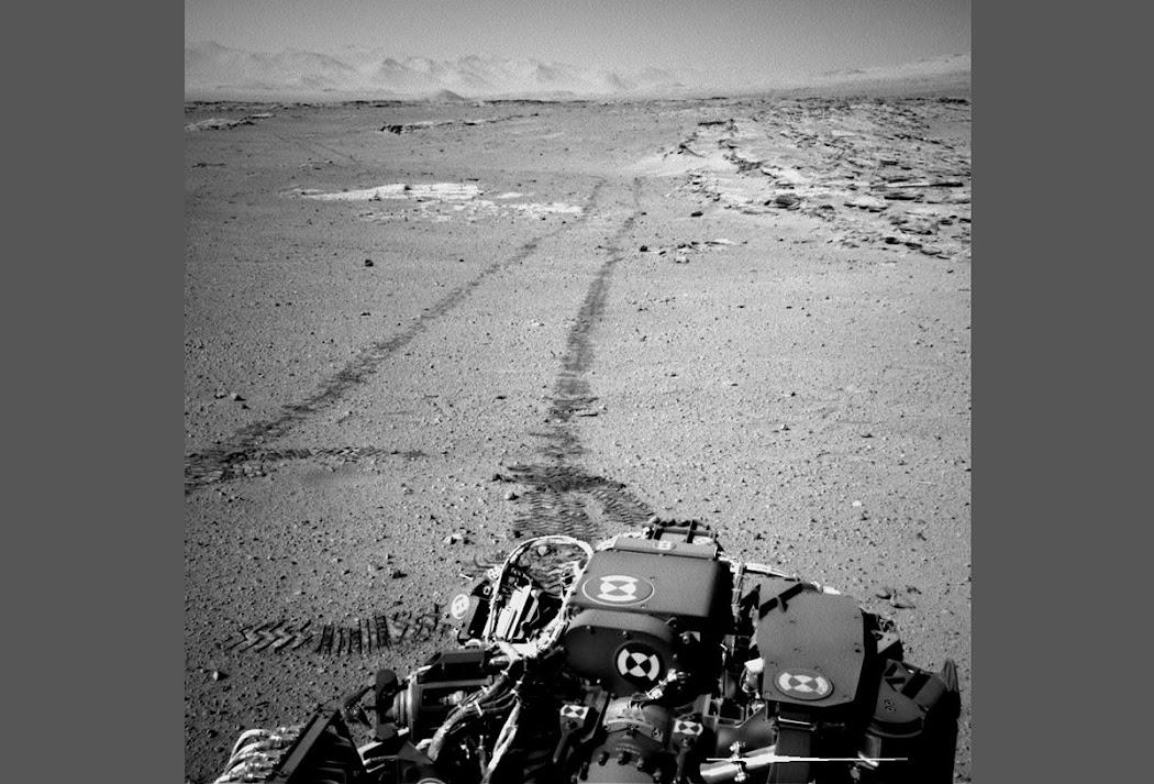 """Tàu Curiosity sử dụng mastcam để nhìn lại chặng đường hơn 100 mét đã đi qua vào sol 548 (ngày 19 tháng 2 năm 2014). Những dãy đá ở bên phải đường bánh xe là một bãi đá lộ thiên được gọi là """"Junda"""", chúng tạo thành những họa tiết thú vị trên mặt đất và được nhìn thấy từ các hình ảnh chụp bởi những tàu vũ trụ bay trên quỹ đạo Sao Hỏa. Để dễ cho bạn hình dung, khoảng cách giữa hai đường bánh xe trong ảnh này là 2,7 mét. Hình ảnh: JPL-Caltech/MSSS/NASA."""