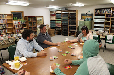 adults playing Apples to Apples card game in library