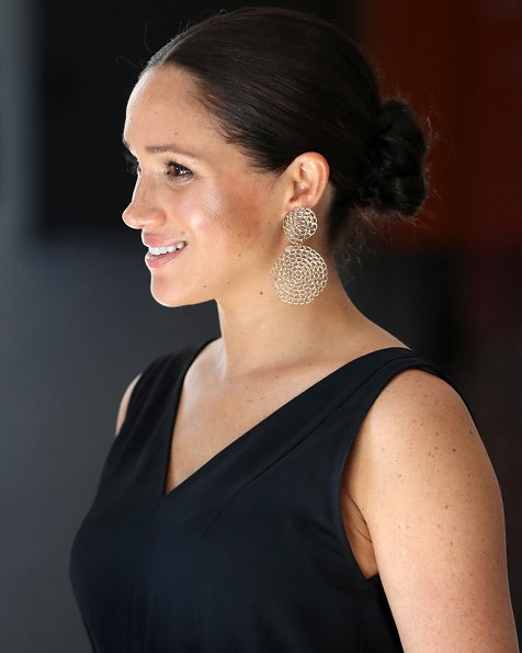 Meghan Markle wore Clup Monaco dremah silk midi dress and Everlane essential goweave jumpsuit. Gas earrings