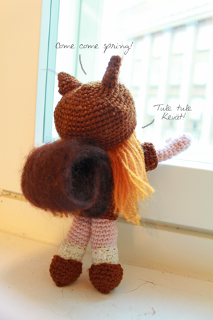 Amigurumi squirrel girl looking out through the window