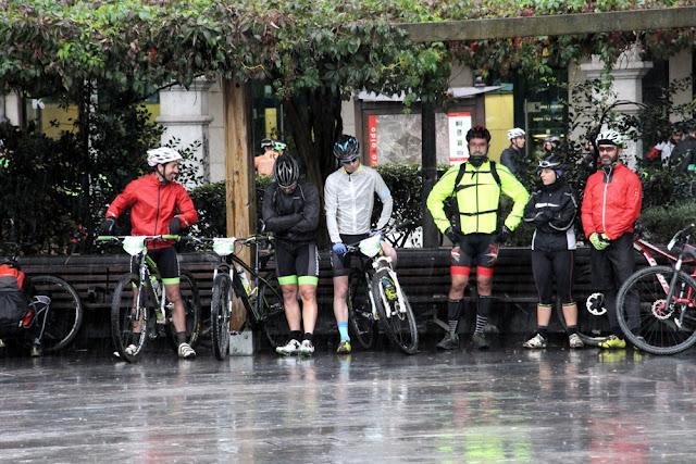 Ciclistas se protegen de la lluvia en las pérgolas de Herriko Plaza