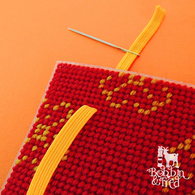 Threading yellow flat elastic through the hole in a sheet of stitched plastic canvas