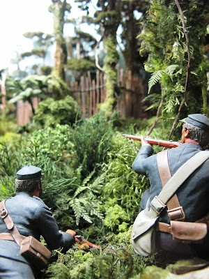Diorama of 19th-century soldiers with muskets in the bush, aiming at a pa fence.