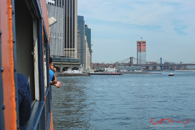 The ferry returns to the Lower Manhattan terminal providing a view of the Brooklyn Bridge and the east river from the port side of the boat. Travel photography by Kent Johnson.