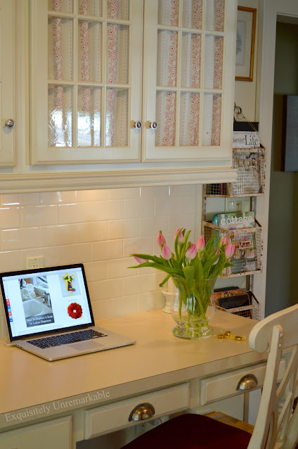 Kitchen desk area with glass cabinets and laptop on desk
