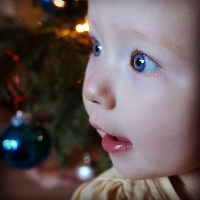 A blue eyed baby in front of a tree