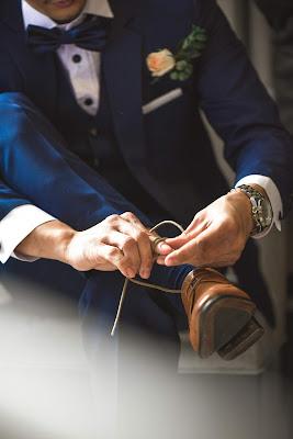 Novio con traje, pajarita y gemelos anudándose los cordones de los zapatos
